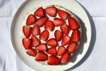 Gluten free almond sponge cake decorated with whip cream and strawberries. Top view. Reklamní fotografie