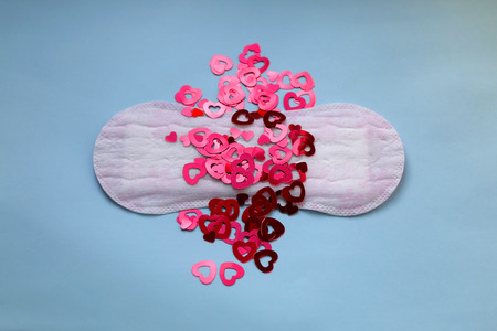 Period pad with red heart shaped sequins symbolizing menstruation. Top view, light blue background.