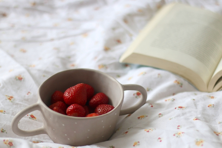 Unrecognizable person holding a bowl of strawberries. Open book on floral sheets. Selective focus. Stockfoto