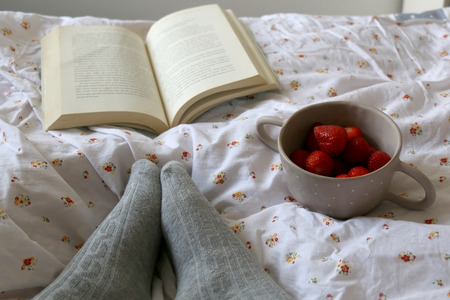 Feet in knit grey socks, bowl of strawberries and book on a bed. Unrecognizable person enjoying leisure time. Selective focus. Stock fotó