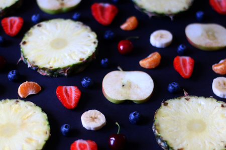 Various fruits and fruit slices on dark background: pineapple,apple, strawberry, banana, blueberry, cherry and tangerine. Selective focus.