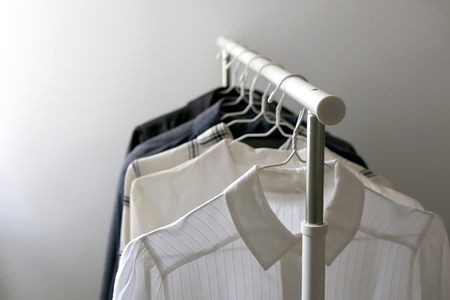 Minimal capsule wardrobe on a clothes rack. Selective focus.