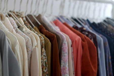 Colorful tops and blouses on a clothes rack. Quirky and whimsical wardrobe. Selective focus.