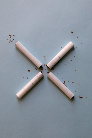 Two broken cigarettes symbolizing stop (X) sign. Smoking cessation concept. Bright blue background.