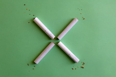 Two broken cigarettes symbolizing stop (X) sign. Smoking cessation concept. Green background. 写真素材