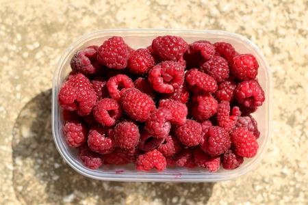 Package full of freshly picked raspberries. Top view.