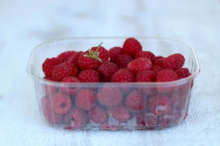 Package full of freshly picked raspberries. Selective focus.