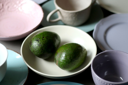 Collection of pottery and kitchenware in muted pastel colors with two avocados. Selective focus.