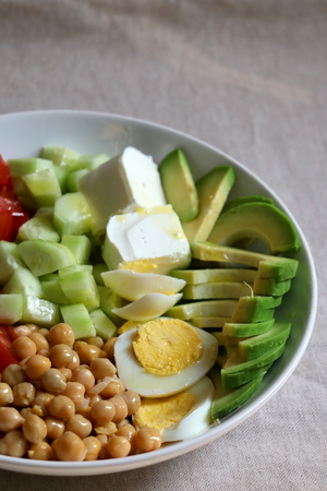 Lunch bowl with avocado, hard boiled egg, chickpea, feta cheese, cucumber, tomato and arugula. Selective focus.