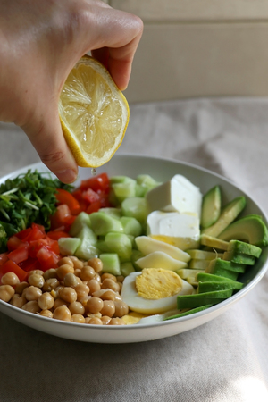 Squeezing lemon juice on lunch bowl with avocado, hard boiled egg, chickpea, feta cheese, cucumber, tomato and arugula. Selective focus. Stock Photo