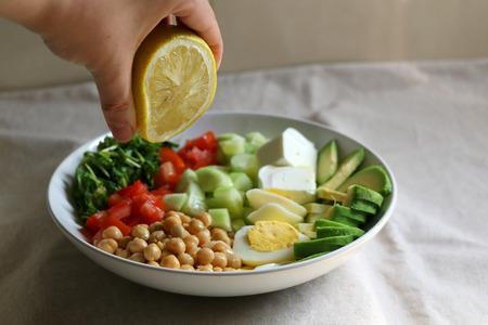 Spremere il succo di limone sulla ciotola del pranzo con avocado, uova sode, ceci, feta, cetriolo, pomodoro e rucola. Messa a fuoco selettiva. Archivio Fotografico