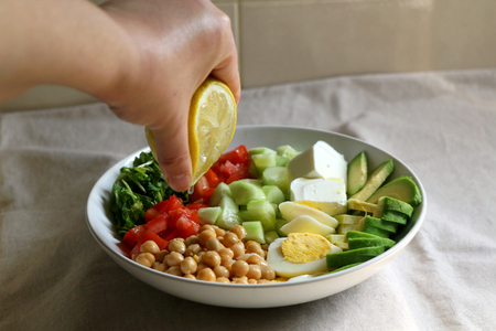 Squeezing lemon juice on lunch bowl with avocado, hard boiled egg, chickpea, feta cheese, cucumber, tomato and arugula. Selective focus. Stockfoto