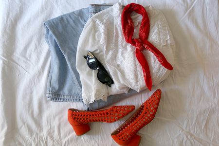 Fashionable outfit with vintage white blouse, worn out jeans, red scarf, red mesh shoes and sunglasses. Flat lay, white linen background.