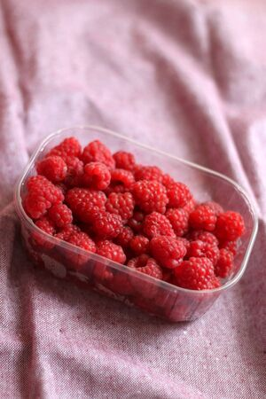 Fresh raspberries in a container. Selective focus, pink background. 免版税图像