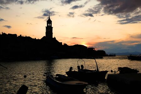 Beautiful sunset in small town Sutivan, on island Brac, Croatia. Silhouettes of historical bell tower, traditional homes and small boats against the colorful cloudy sky.