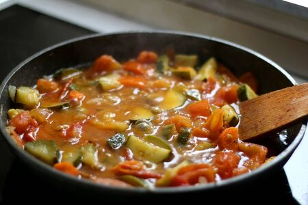 Cooking vegetables in a pan: zucchini, tomato and carrot. Selective focus.
