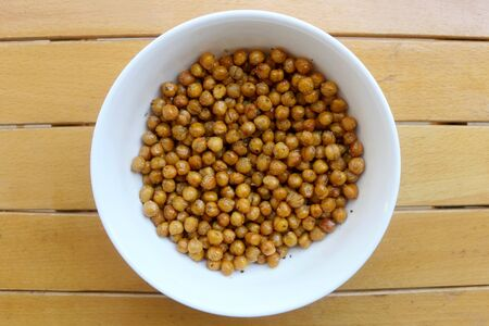 Bowl of roasted crispy chickpeas on wooden table. Top view.
