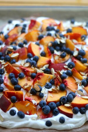 Chocolate Pavlova cake with whipped cream, peaches, blueberries and almonds. Selective focus.