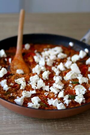 Pot of orzo pasta, with tomato sauce, vegetables and feta cheese. Selective focus.