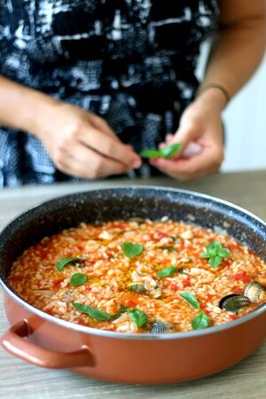 Unrecognizable person putting basil leaves in pot of orzo pasta, with tomato sauce, vegetables and seafood. Selective focus.