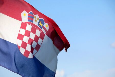 Flag of Croatia blowing in the wind. Bright blue sky in the background.