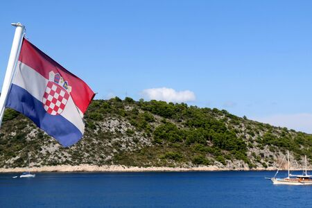 Flag of Croatia blowing in the wind. Croatian coast and traditional sailing boat in the background. Stock fotó