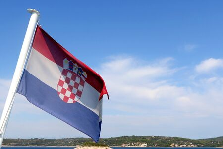 Flag of Croatia blowing in the wind. Croatian coast and islands in the background. Stock fotó