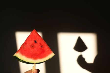 Unrecognizable person holding a slice of watermelon, illuminated by sunlight. Selective focus.