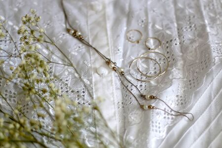 Vintage white lace blouse, silver and gold jewelry and white gypsophila flowers. Selective focus. Imagens