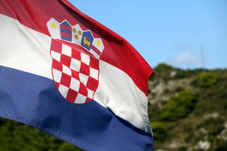 Flag of Croatia blowing in the wind. Hill and bright sky in the background. Selective focus.