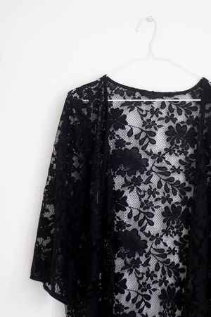 Black lace kimono top hanging in front of white wall.