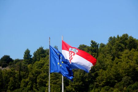 Flags of Croatia and European Union, blowing in the wind. Pine trees and bright sky in the background.