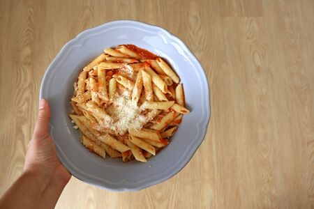 Hand holding a plate of pasta with tomato sauce and parmesan cheese. Top view. Stock fotó