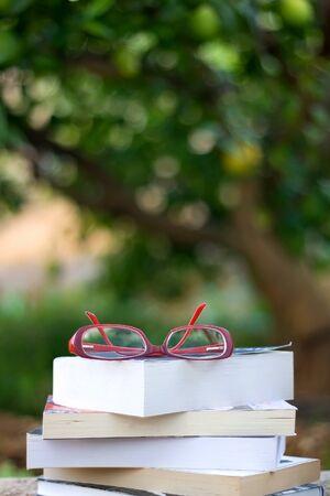Pila di libri e occhiali da lettura rossi all'aperto. Messa a fuoco selettiva, bokeh naturale verde.