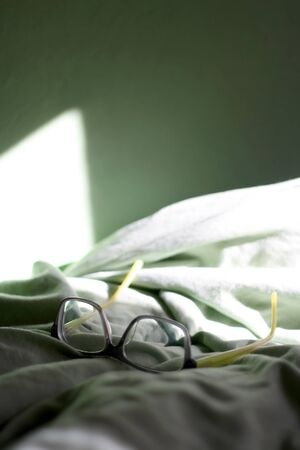 Grey and green reading glasses on a bed with green sheets and green wall. Selective focus.