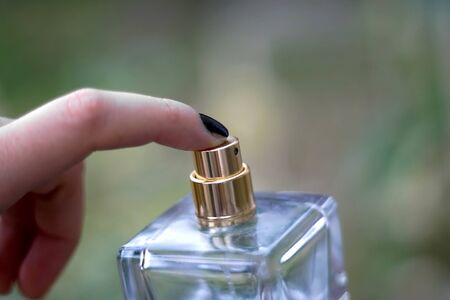 Spraying perfume from a glass bottle. Selective focus, natural green background.