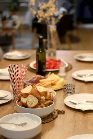 Table set for dinner party with plates, bread, ice, paper straws and spread. Selective focus.