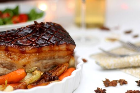 Pork belly roast and roasted vegetables on a holiday table. Selective focus. Stock Photo