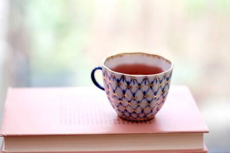 Kopje thee op roze boek. Selectieve aandacht. Stockfoto