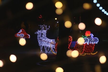 Outdoor Christmas decorations, shaped liked Santa's sleight, illuminated at night. Selective focus, defocused bokeh in the foreground.