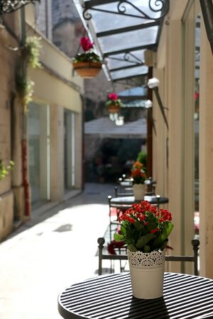 Flowers and tables in a picturesque alley in central Split, Croatia.