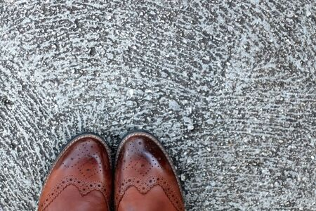 Detail of brown leather boots on a concrete floor. Top view.