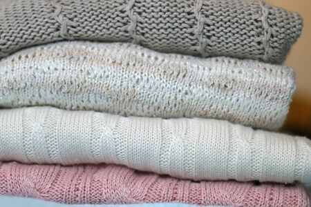 Pile of pastel and neutral colored sweaters on mint green background. Selective focus.