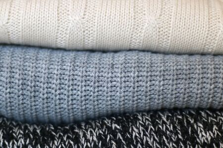 White, gray and black sweaters, close-up.