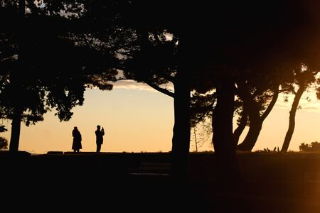 Silhouettes of unrecognizable people enjoying the sunset in Sustipan park in Split, Croatia.