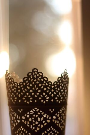 Intricate candle holder illuminated by warm sunset light. Selective focus.