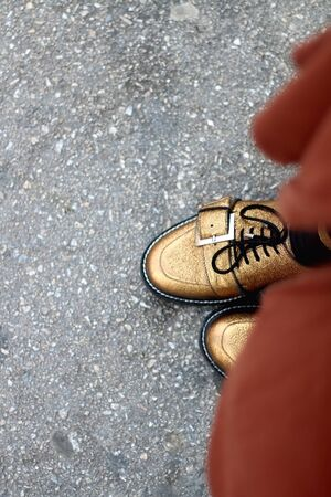 Unrecognizable person wearing golden flat shoes on the street. Top view, Selective focus.