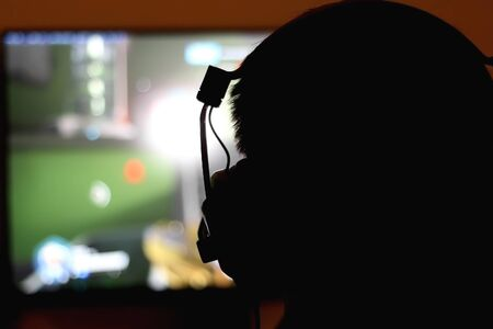 Silhouette of an unrecognizable man with headset playing computer games. Selective focus.