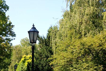Vintage lamp in park in Zagreb, Croatia. Selective focus, green bokeh.