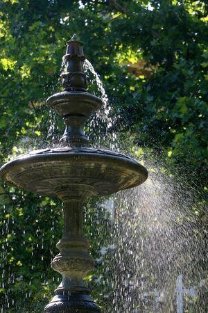 Fountain in the park Zrinjevac, in Zagreb, Croatia. Selective focus, green bokeh. Stock Photo
